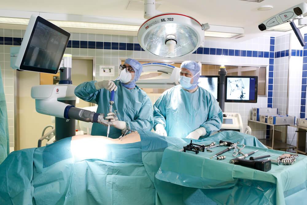 Während der Wirbelsäulenoperation schauen unsere Ärzte die in Echtzeit geleiferten Informationen auf dem Bildschirm an.